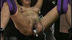 Slave hangs in suspension while her lips and cunt get teased