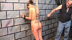 Nicole is chained to the dungeon wall and whipped by her master